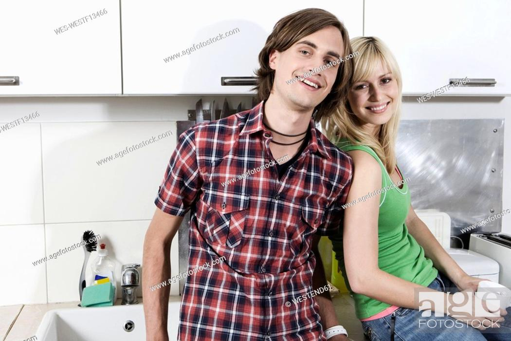 Stock Photo: Germany, Berlin, Young couple in kitchen, smiling, portrait.