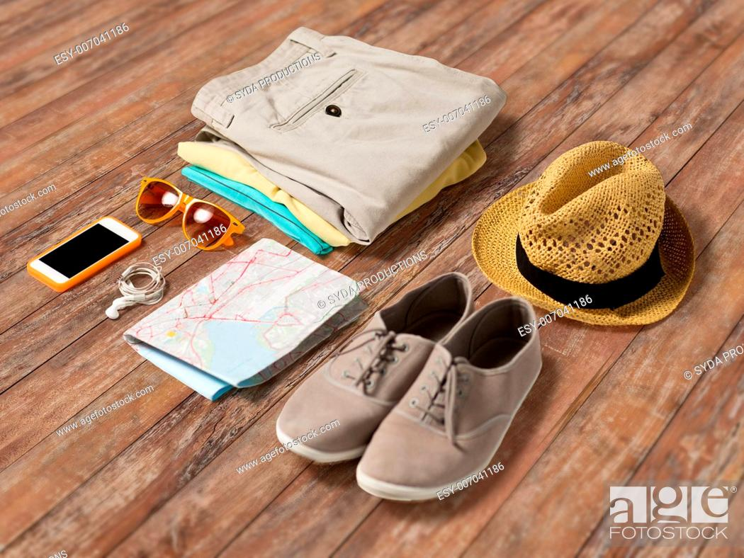 Stock Photo: summer vacation, tourism and objects concept - close up of clothes, smartphone, personal stuff and travel map on wooden floor.