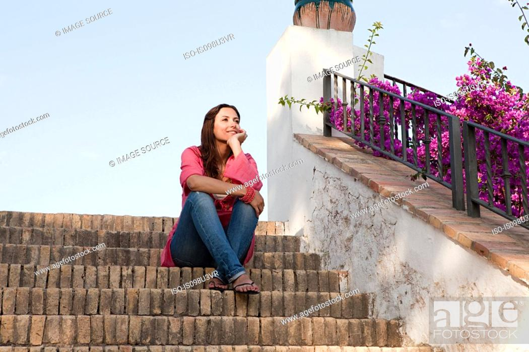 Stock Photo: Young woman sitting on steps.