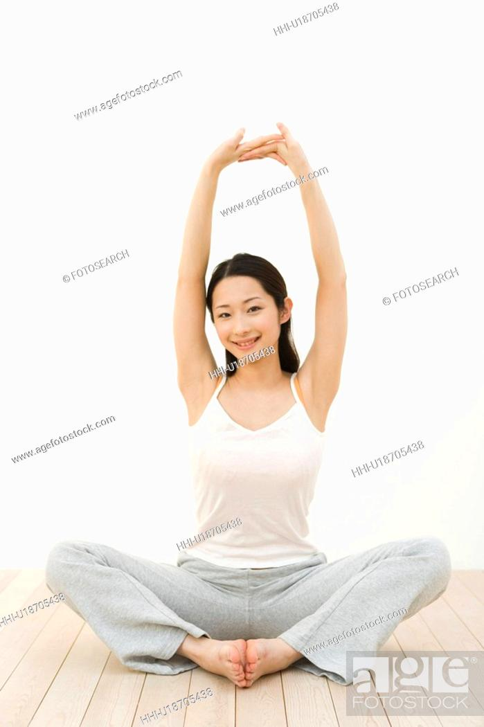 Stock Photo: Portrait of a woman sitting cross-legged and stretching arms, front view, white background.
