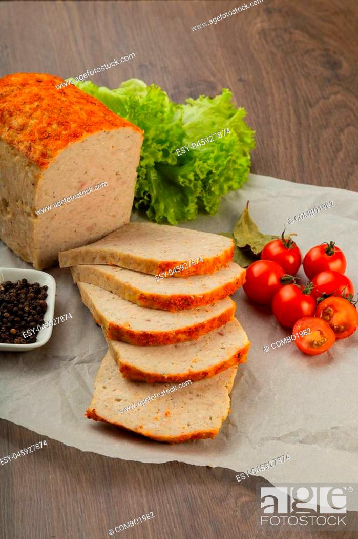 Stock Photo: Meat product in the form of bread with spices and on baking paper.