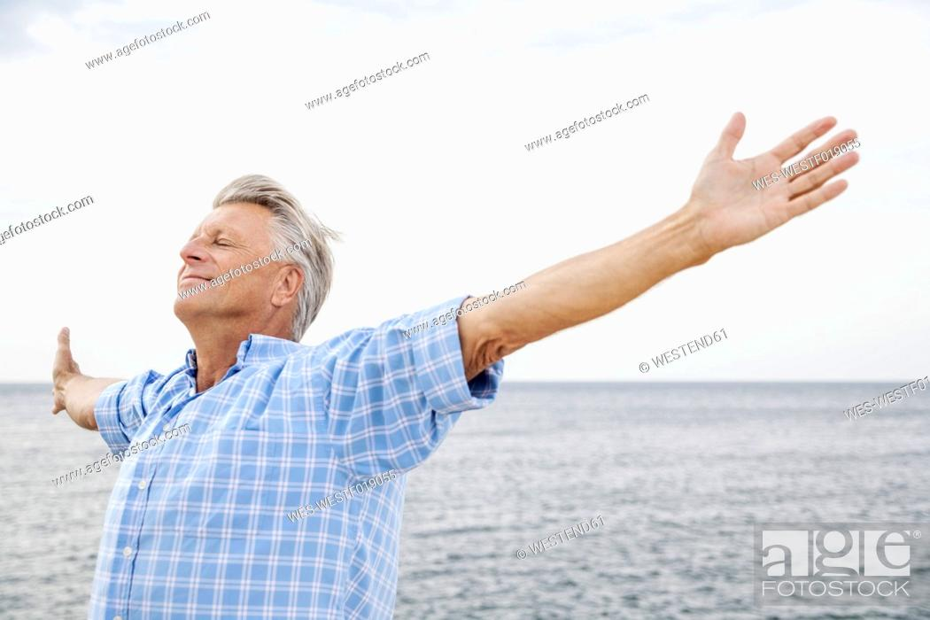 Stock Photo: Spain, Senior man stretching on beach.