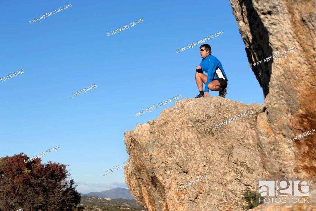 Stock Photo: Man kneeling on a rock ledge.