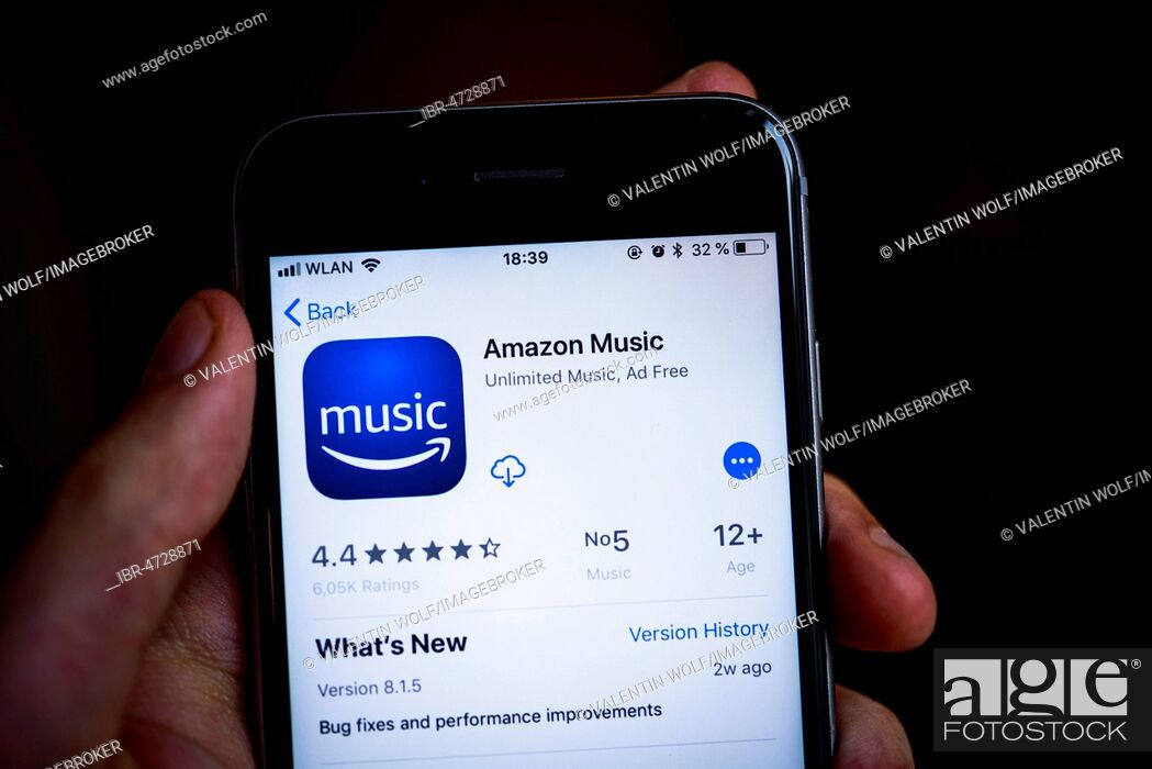 Hand holding iPhone, Amazon Music App in the Apple App Store