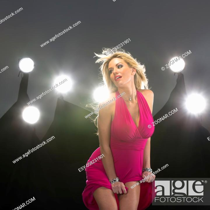 Stock Photo: An attractive blonde model poses in a studio environment with lights in the background.An attractive blonde lingerie model poses in a studio environment with.