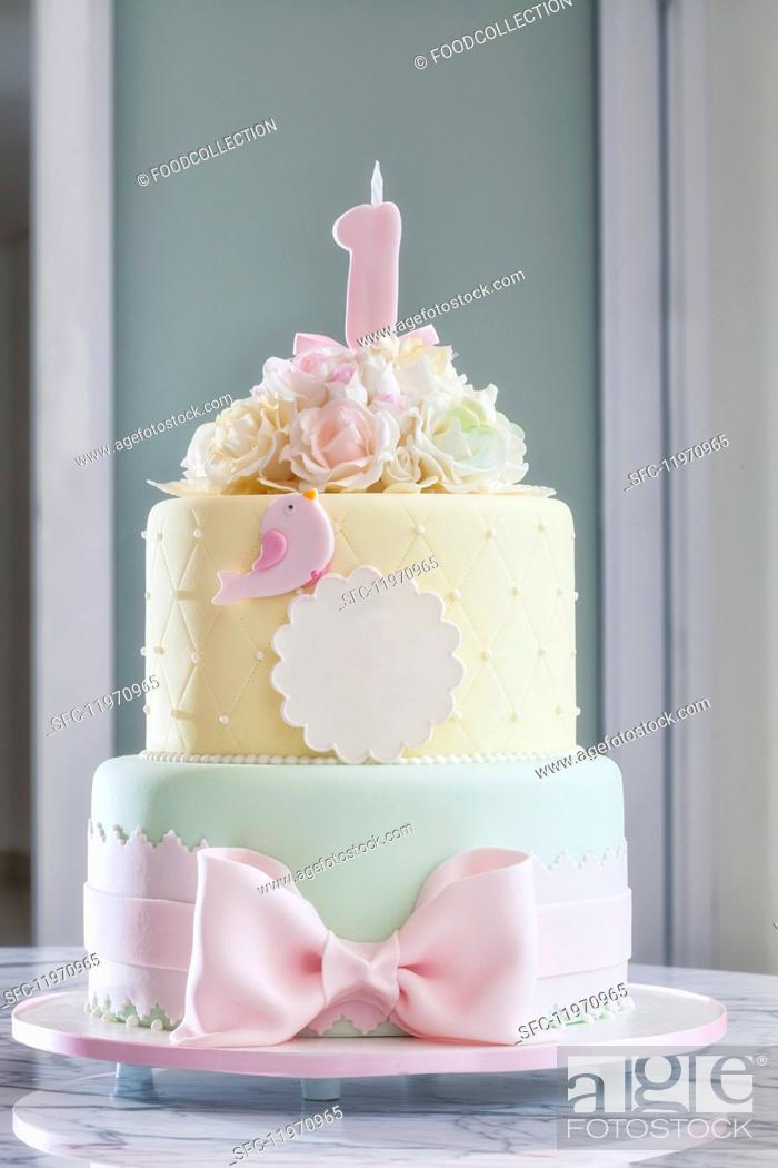 Stock Photo: A festively decorated birthday cake in delicate pastel tones.