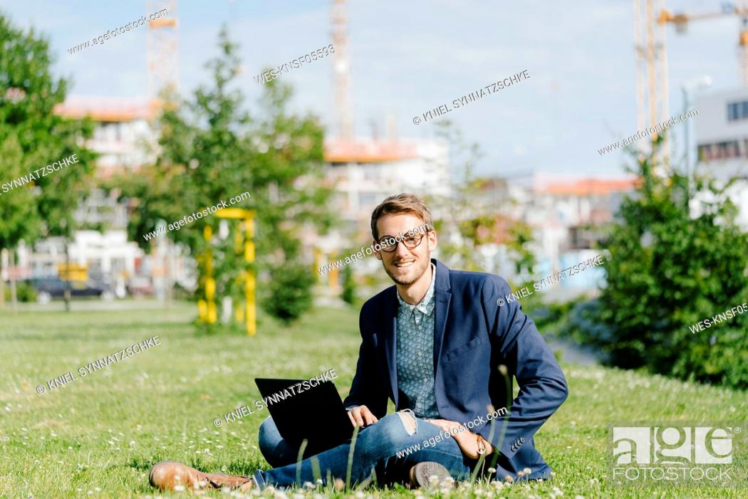 Stock Photo: Young businessman sitting in park, using laptop.