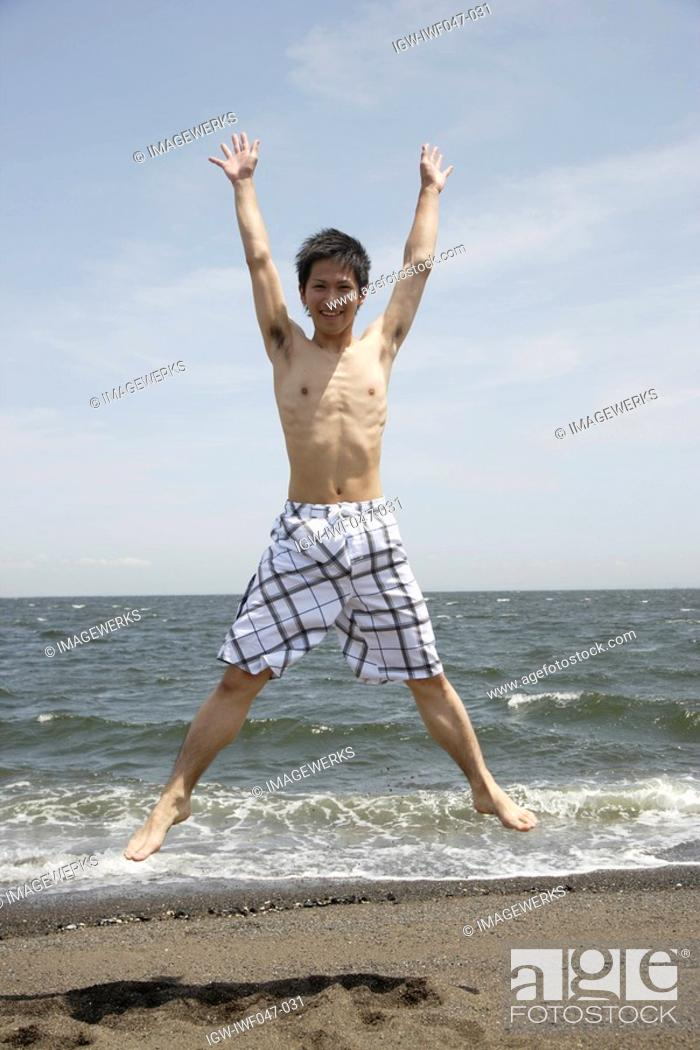 Stock Photo: Portrait of a young man jumping on beach.
