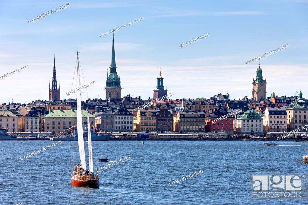 Stock Photo: Tourists in sailboat with churches in the background, Gamla Stan, Stockholm, Sweden.