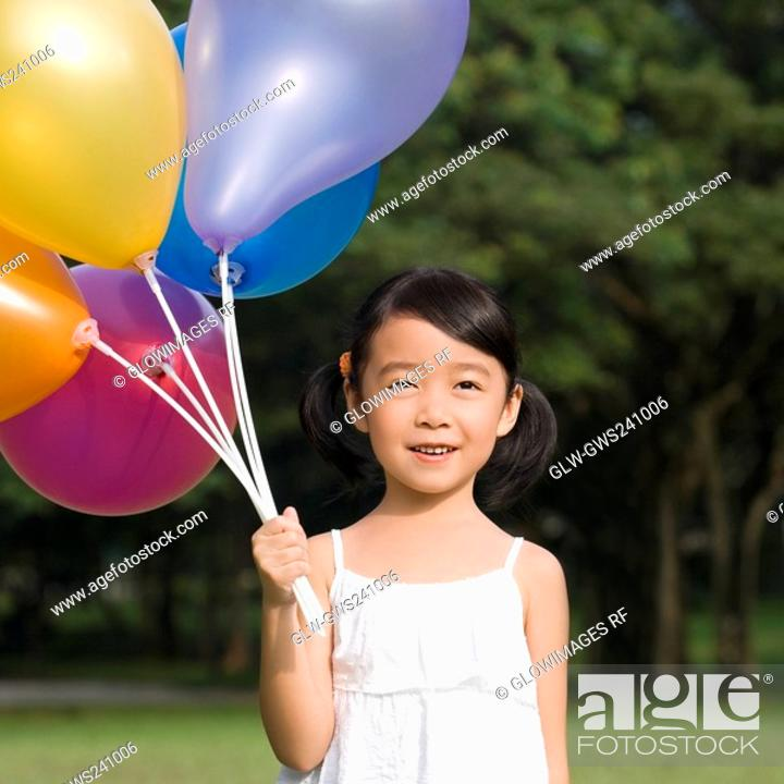 Stock Photo: Close-up of a girl holding balloons and smiling.