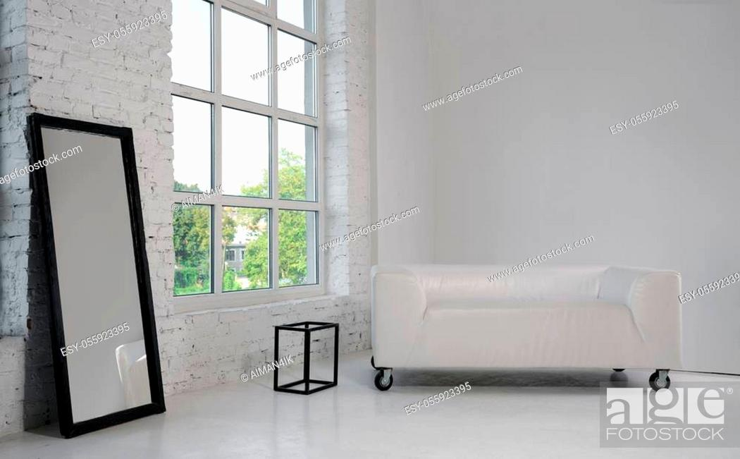 Stock Photo: Modern white sofa and large black framed mirror in white minimalist room with big window.
