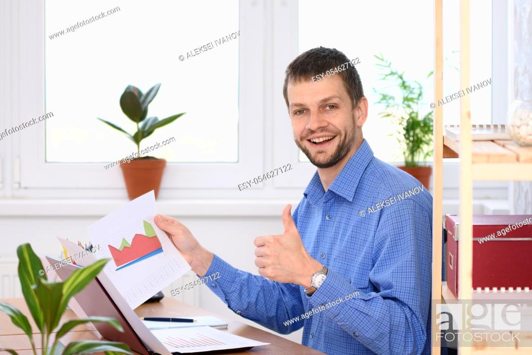 Stock Photo: Young businessman shows charts and thumb up.