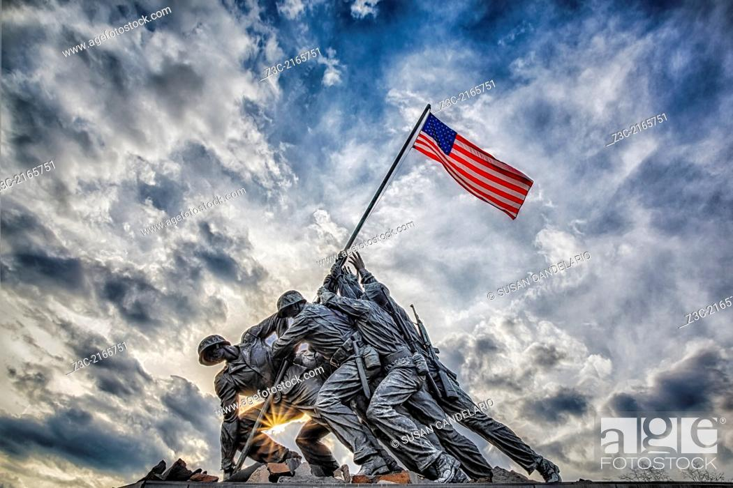 Imagen: The Marine Corps War Memorial also called the Iwo Jima Memorial in Arlington, Virginia, with dramatic storm clouds in the background and a starburst at sundown.