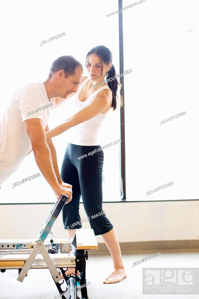 Stock Photo: Personal trainer guiding man on pilates equipment.