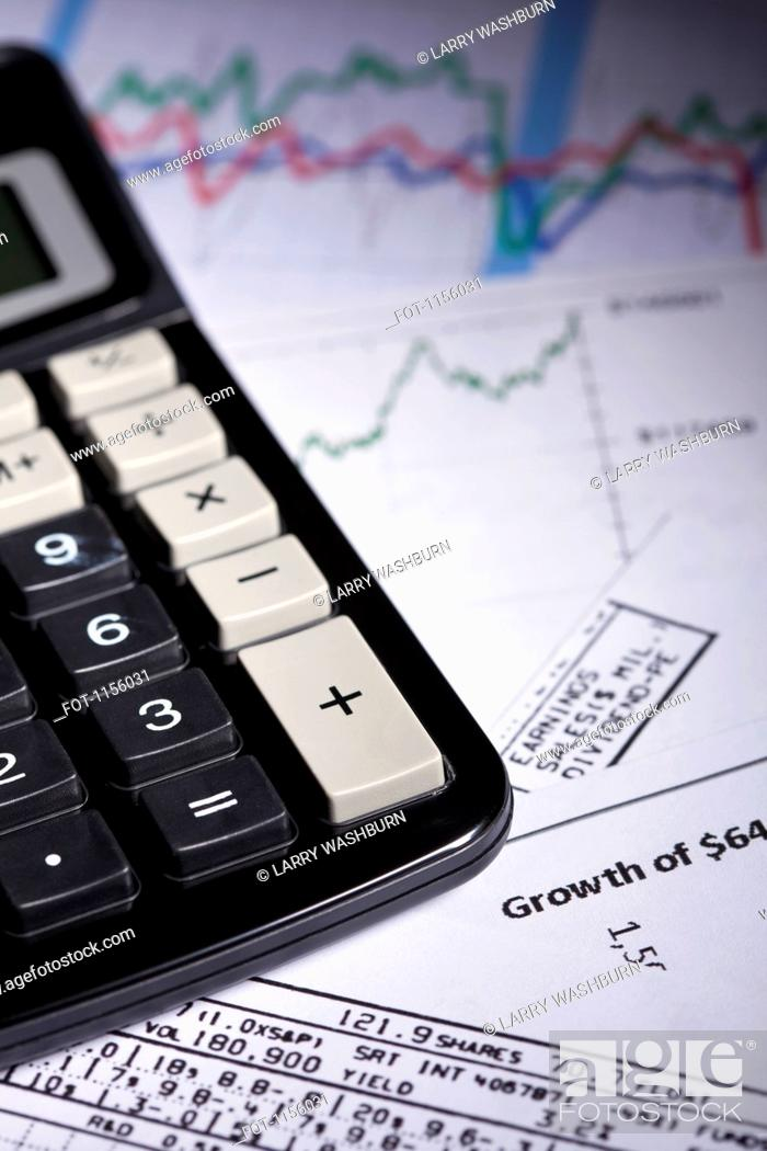 Stock Photo: A calculator on top of a mess of papers with stock market data.