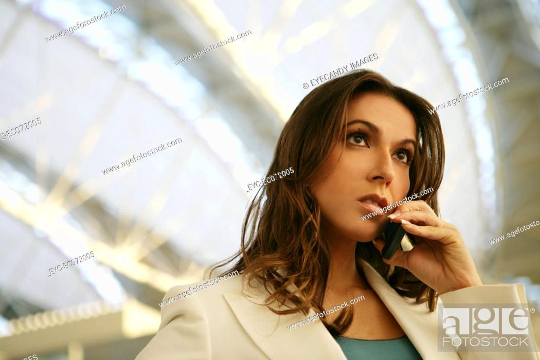 Stock Photo: Young woman in airport on the phone.