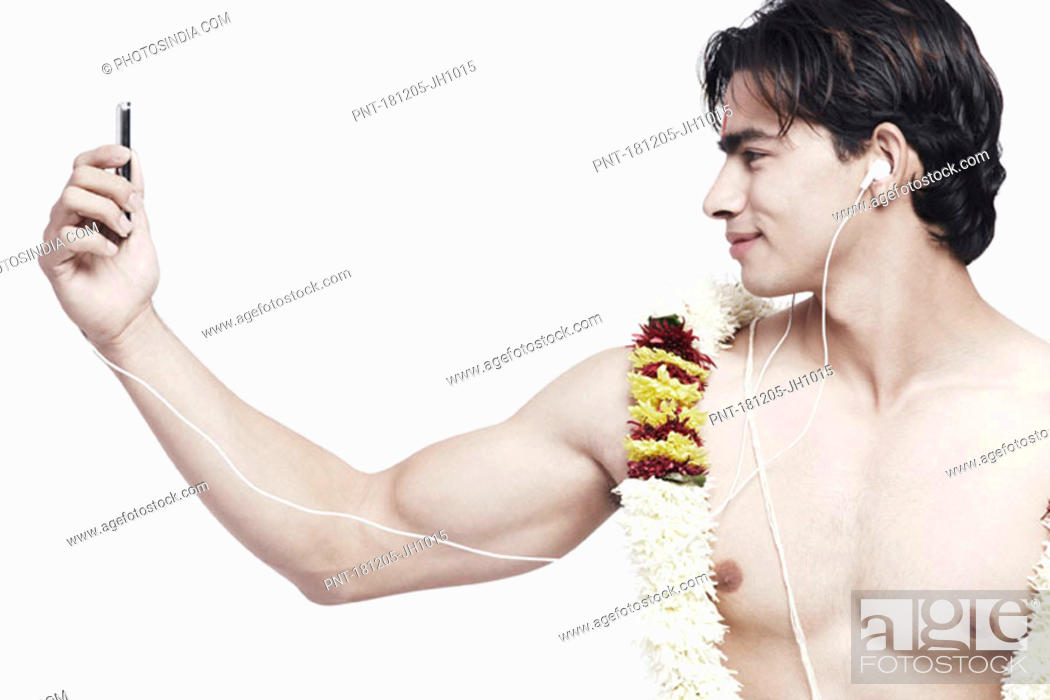 Stock Photo: Close-up of a young man listening to an MP3 player.