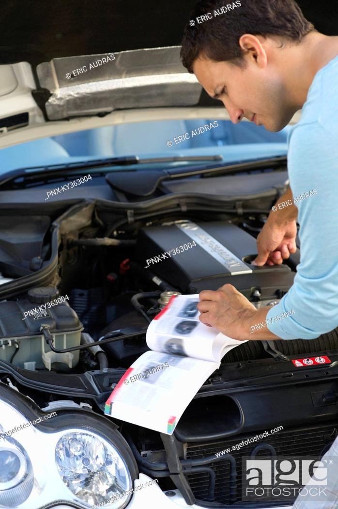 Stock Photo: Mid adult man looking at broken car engine.