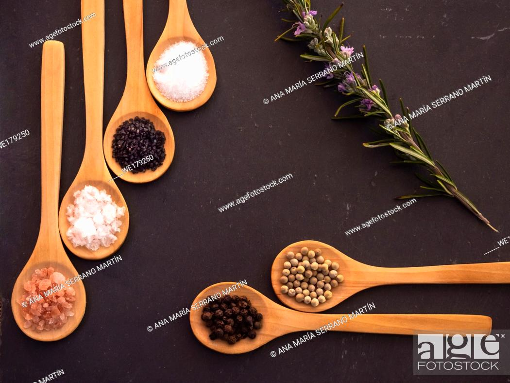 Stock Photo: Wooden spoons with himalayan salt, black hawaii salt, common salt, salt flakes, peppercorns and a rosemary twig on a slate plate.
