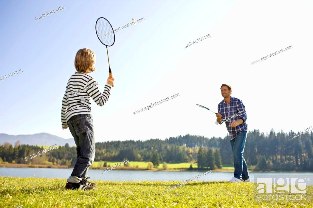 Imagen: Father and son playing badminton near lake.