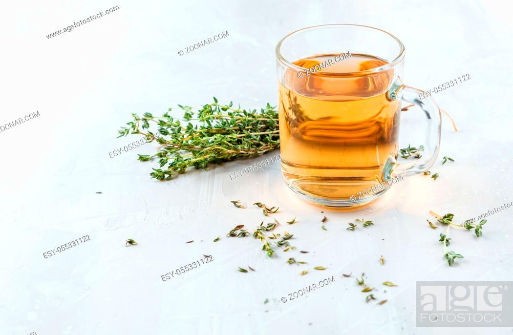 Stock Photo: Transparent glass cup of herbal tea with thyme and sprigs of thyme tied in a bunch on a white background.