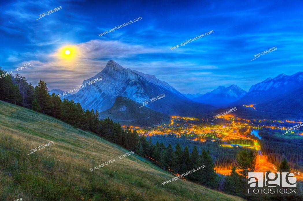 Stock Photo: The supermoon of August 10, 2014 rising behind Mt. Rundle and Banff townsite, as shot from the Mt. Norquay viewpoint looking south over the valley.