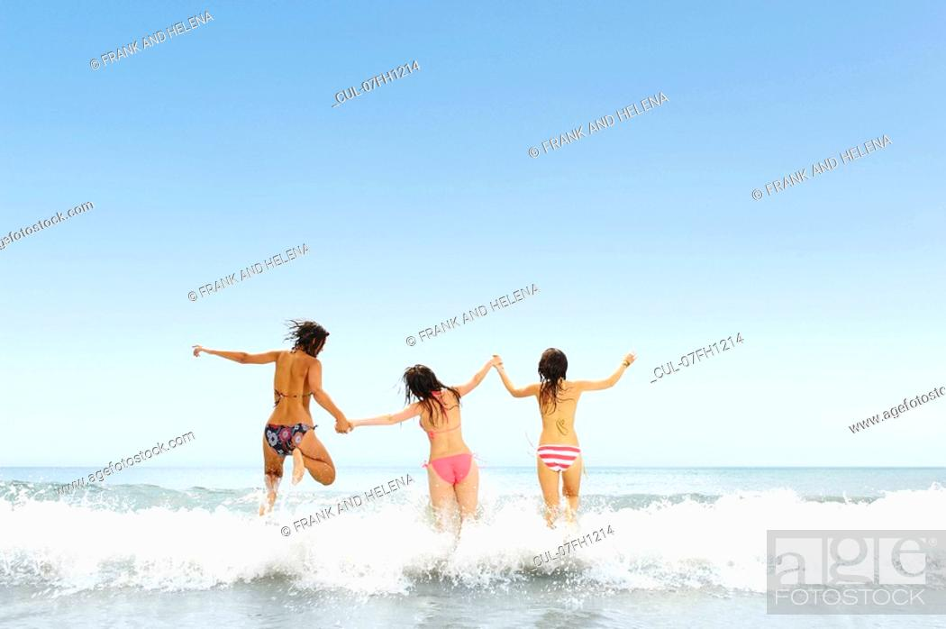Stock Photo: Three girls jumping over wave.
