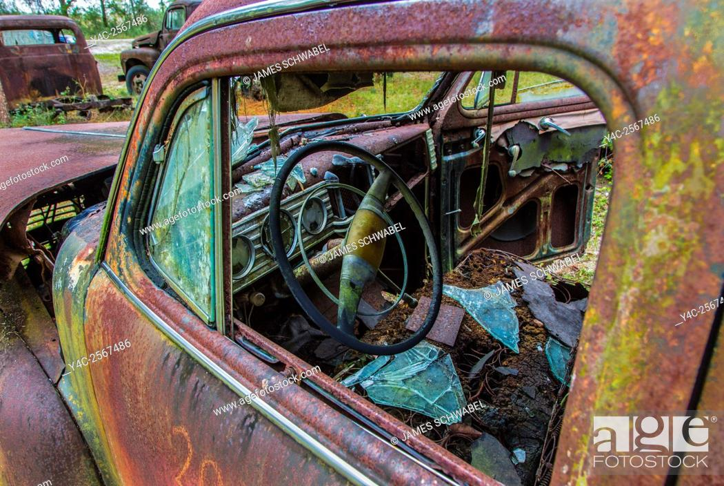 Imagen: Old rusted trucks and cars.