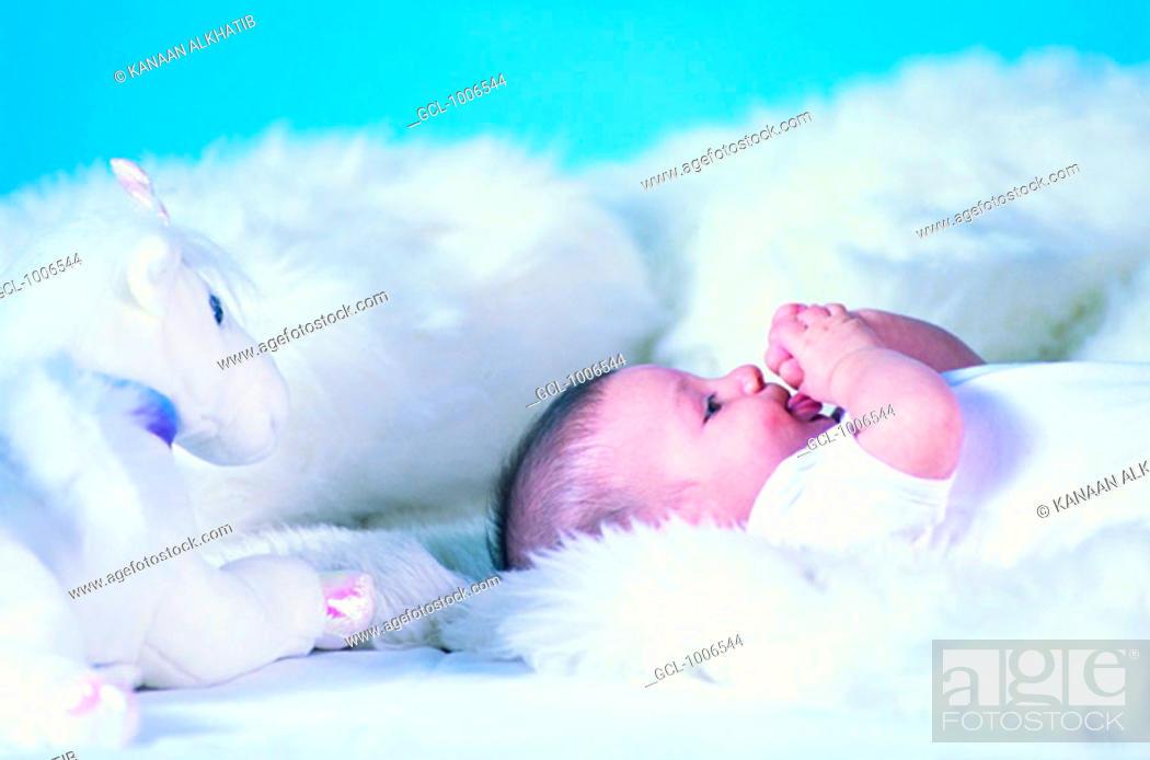 Stock Photo: Baby lying on white fluffy blanket.