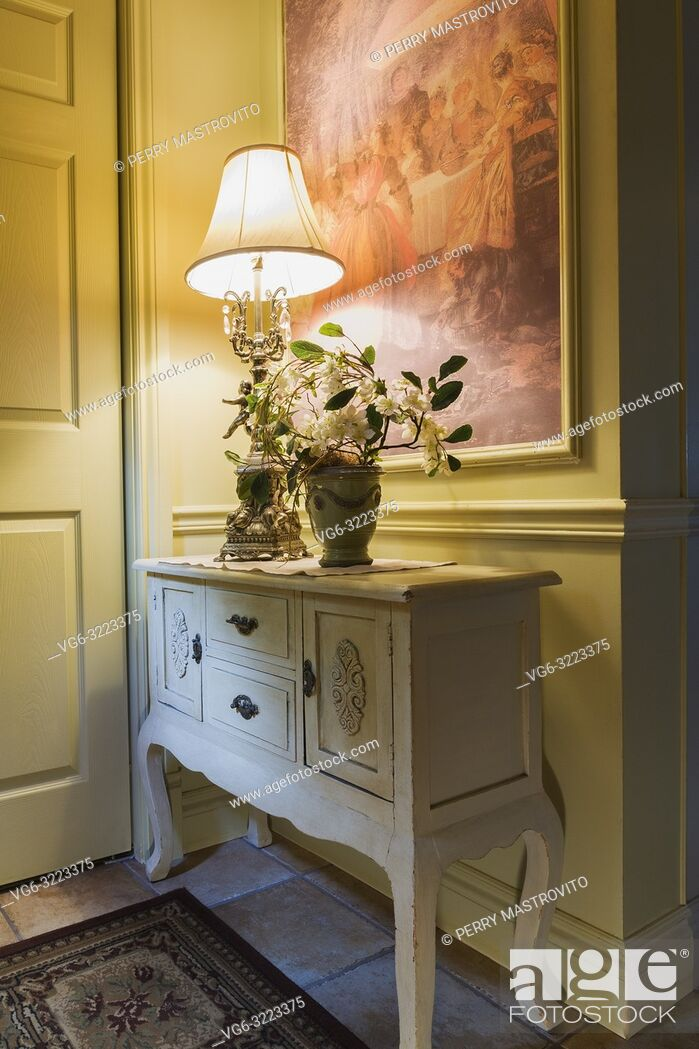 Stock Photo: Antique wooden console with lamp and flower vase in the kitchen entryway inside a 2006 reproduction of a 16th century Renaissance castle style residential home.
