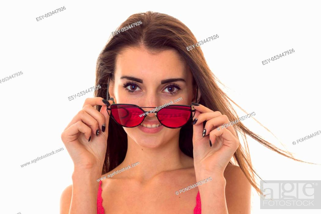 Stock Photo: portrait of beauty young girl in pink light shirt looking at the camera and take off sunglasses isolated on white.
