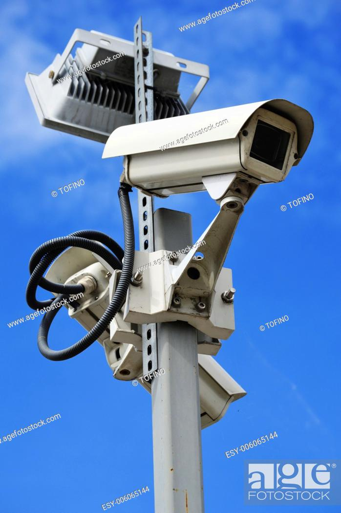 Stock Photo: Hi-tech dome type camera over a blue sky.
