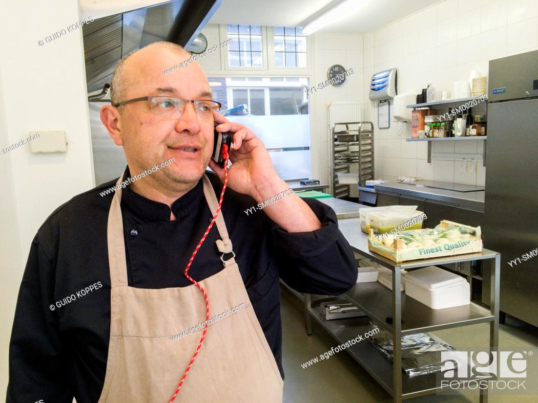Stock Photo: Tilburg, Netherlands. Pro chef making an order by phone for new and fresh ingredients for his dishes.