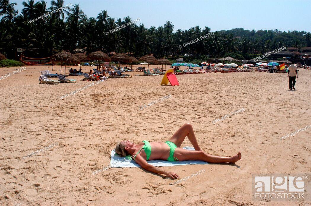 A foreign tourist enjoying sun bath on the Sinquerim beach of Goa