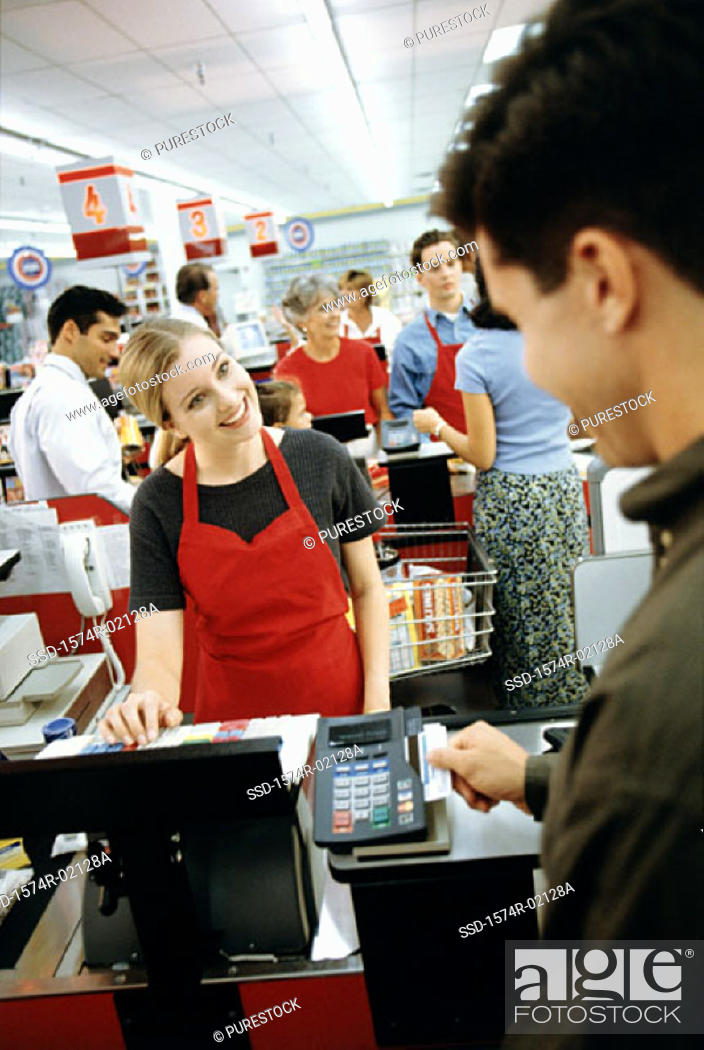 Stock Photo: Young man using a credit card machine at a checkout counter in a supermarket.