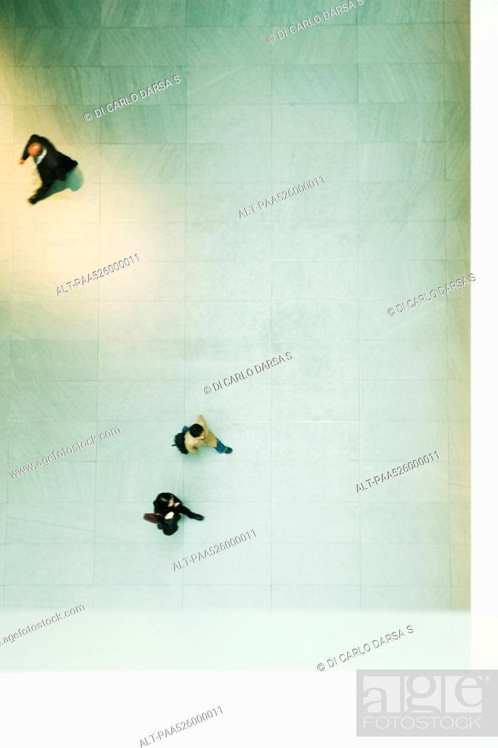 Stock Photo: Pedestrians walking across floor of large lobby, viewed from directly overhead.