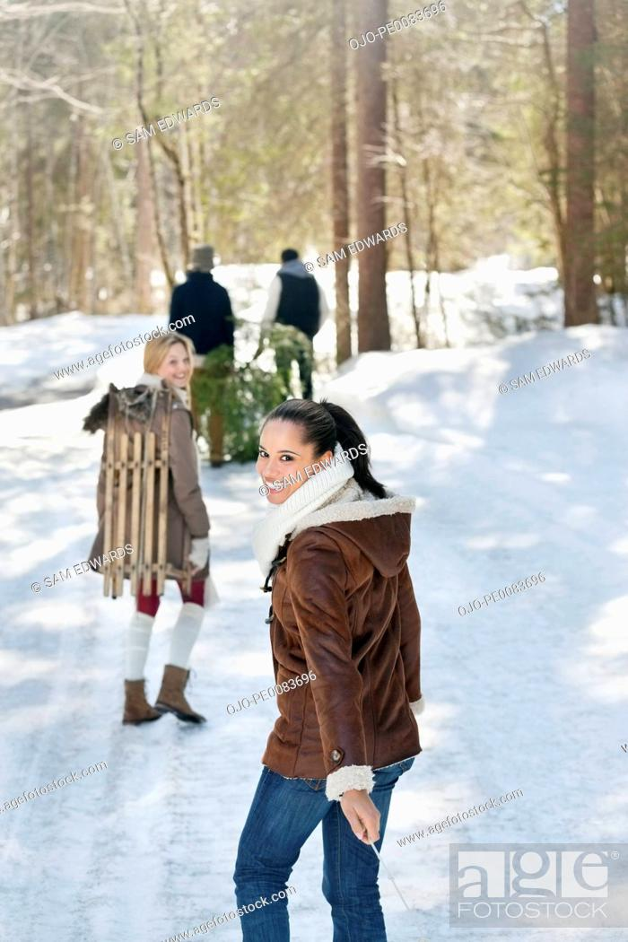 Stock Photo: Smiling friends with fresh cut Christmas tree and sled in snowy woods.