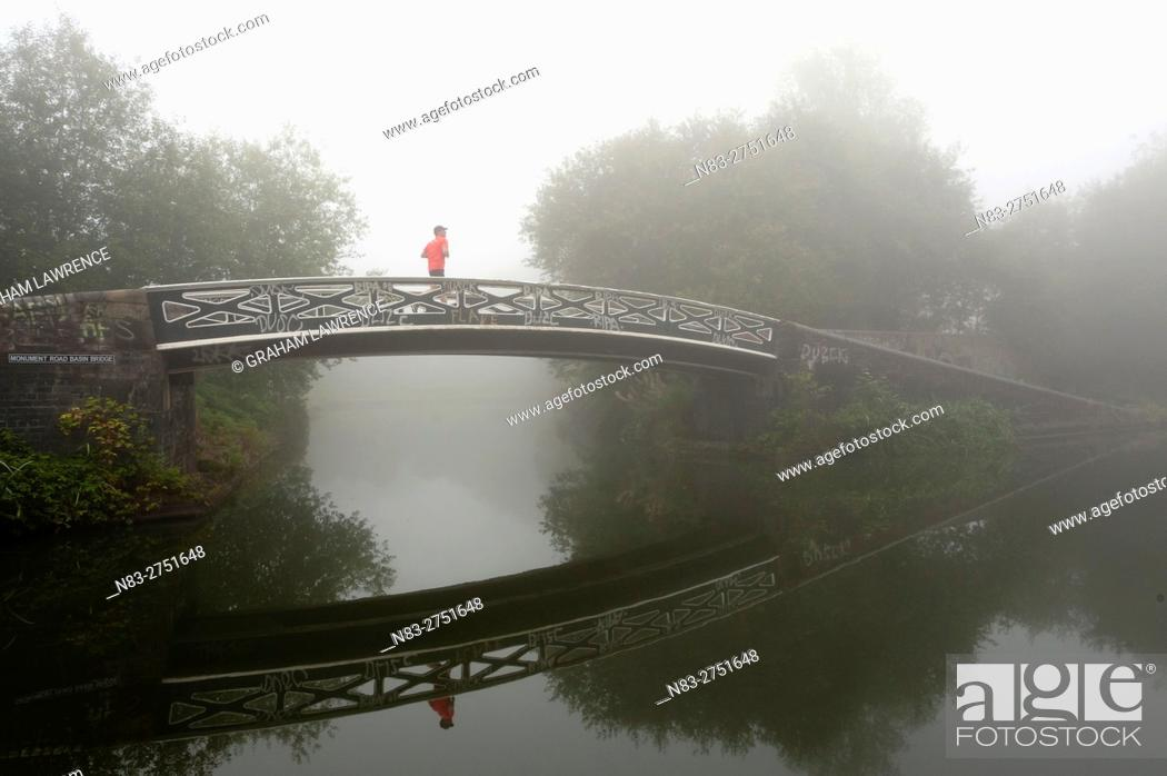 Stock Photo: A jogger on a bridge on Birmingham Canal Navigations, (BCN) Birmingham, West Midlands, UK.