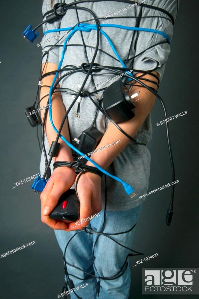 Stock Photo: Teenager with long hair tied up with computer cables.