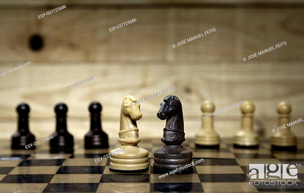 Stock Photo: Faced chess horses and chess pawns with chess board.