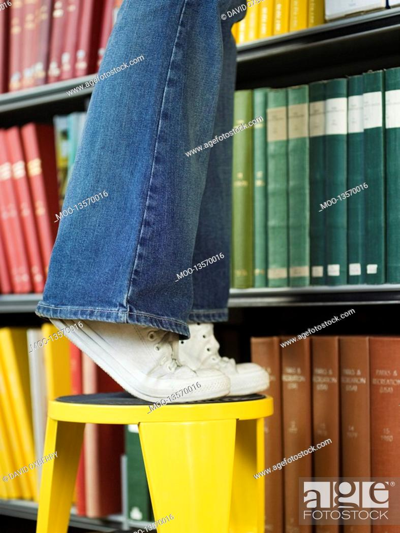 Stock Photo: Young woman standing on stool reaching for book low section.