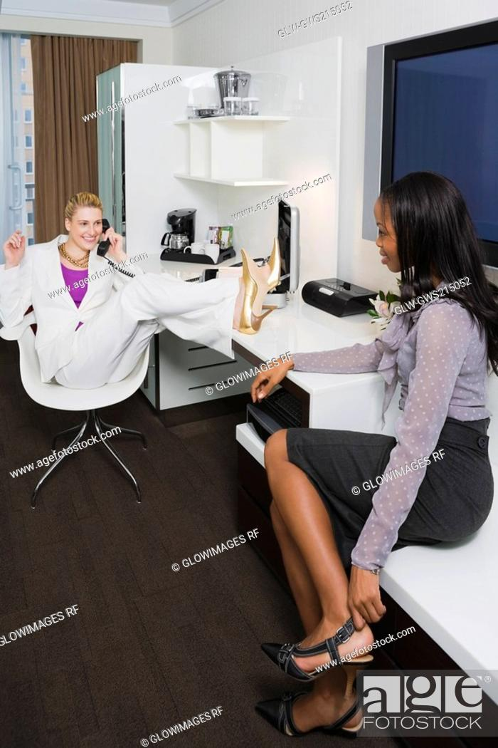 Stock Photo: Two businesswomen looking at each other and smiling.