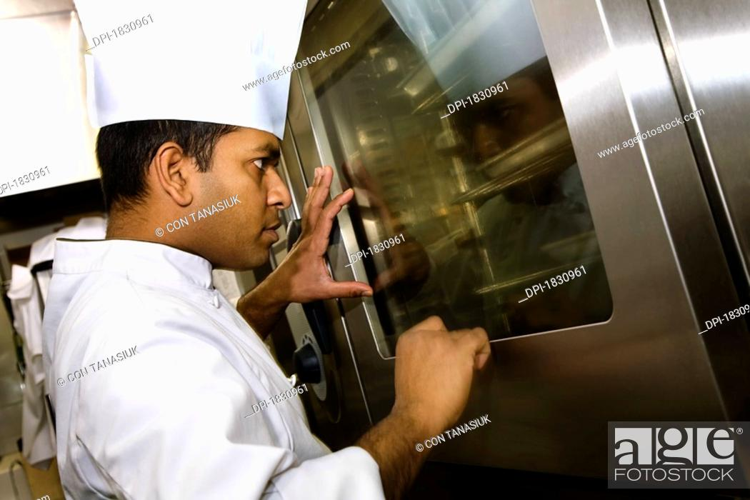Stock Photo: A chef looking into the oven.