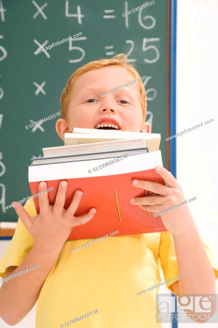 Stock Photo: Portrait of a schoolboy holding a stack of books and smiling.