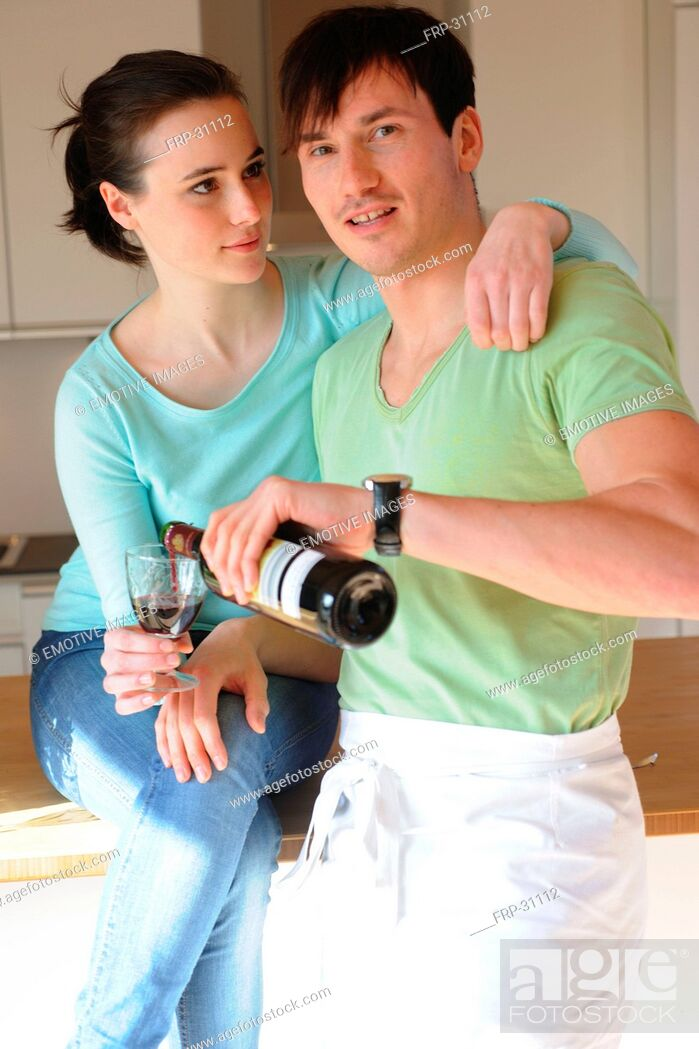 Imagen: Young couple drinking red wine in kitchen.