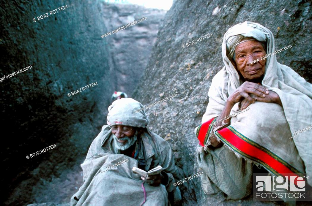 Stock Photo: Old people pray outside of the rock carved chruches of Lalibela.