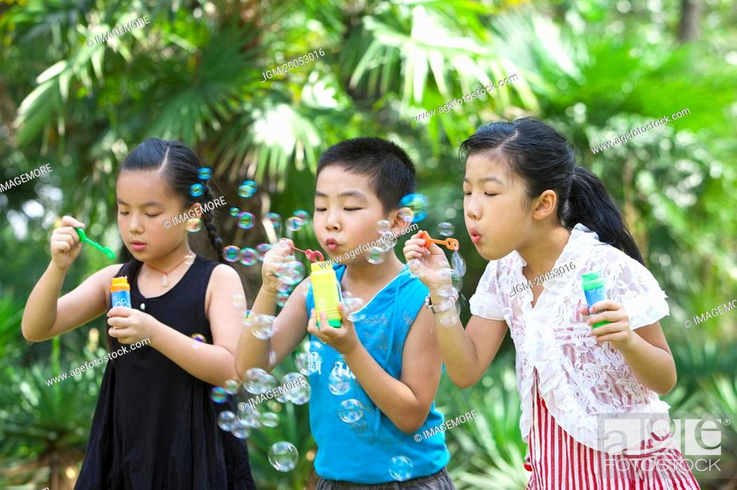 Stock Photo: Three children standing in a row and blowing bubbles together.