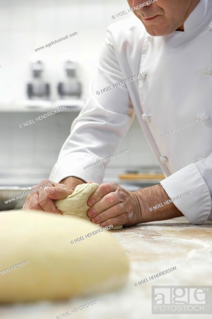 Stock Photo: Chef preparing dough in kitchen.