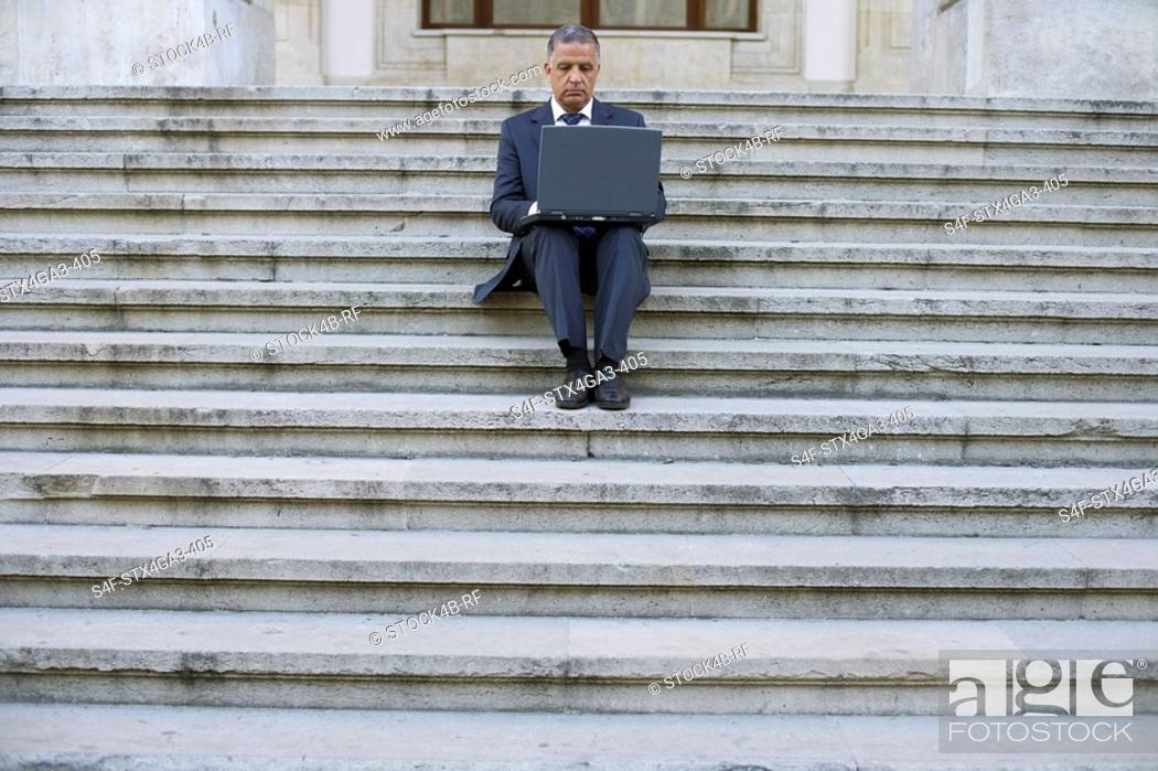 Stock Photo: Man with laptop sitting on a stairway.