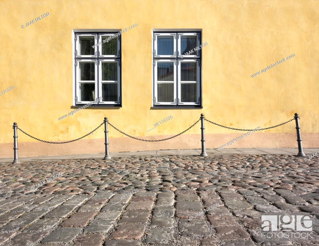Stock Photo: Chain railing, building facade and pedestrian walkway with windows. Cobbled street in old town in Tallinn, Estonia.